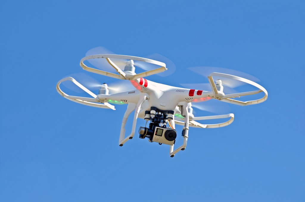 White drone hovering the blue sky